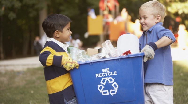 Two boys carrying recycling container